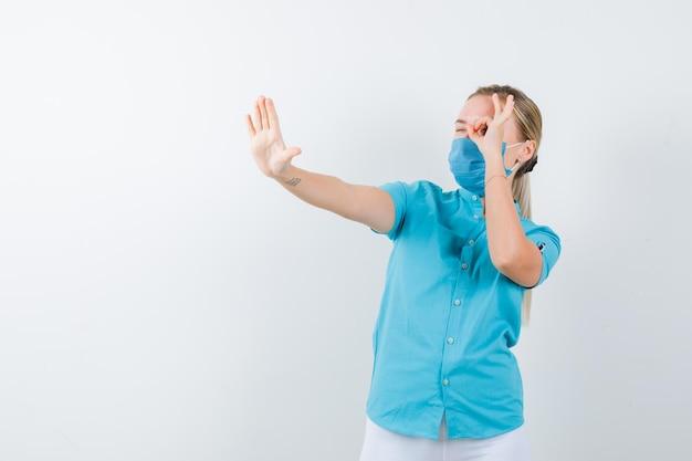 Junge blonde frau, die ein ok-zeichen auf dem auge zeigt, während sie in freizeitkleidung eine stopp-geste macht