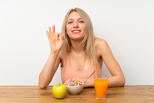 Junge blonde frau, die ein okayzeichen mit den fingern zeigend frühstückt