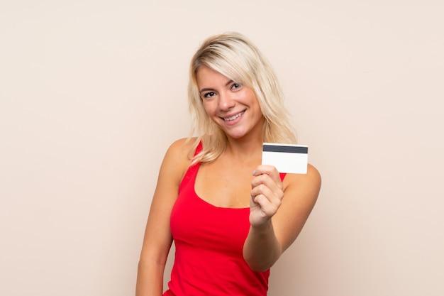 Junge blonde frau, die eine kreditkarte anhält