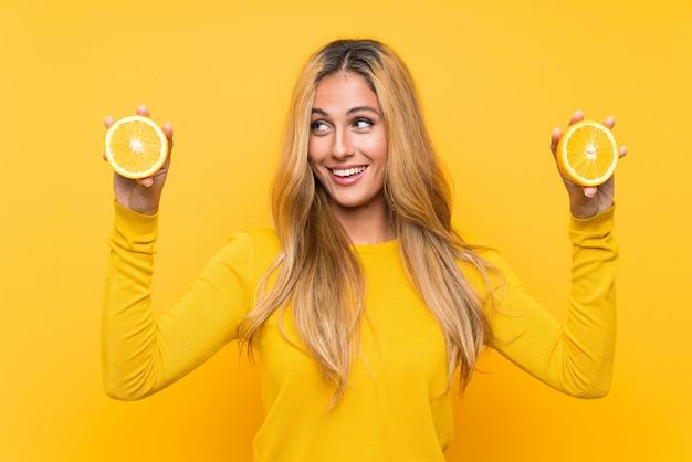 Junge blonde frau, die eine orange über gelber wand anhält