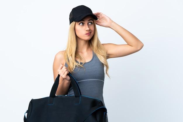 Junge blonde frau, die eine sporttasche über weißer wand hält, die zweifel und mit verwirrendem gesichtsausdruck hat
