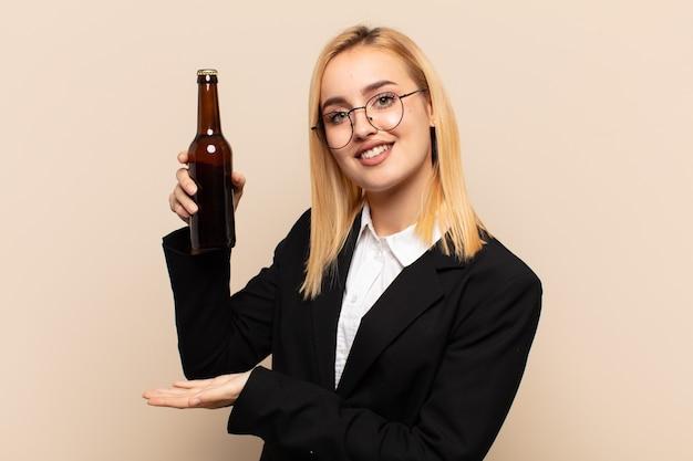 Junge blonde frau, die einen gegenstand mit beiden händen auf seitenkopierraum hält, einen gegenstand zeigend, anbietet oder bewirbt