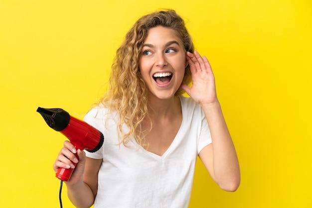 Junge blonde frau, die einen haartrockner isoliert auf gelbem hintergrund hält und etwas hört, indem sie die hand auf das ohr legt