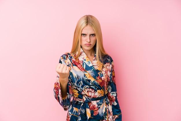Junge blonde frau, die einen kimono-pyjama trägt, der faust zur kamera zeigt, aggressiver gesichtsausdruck.