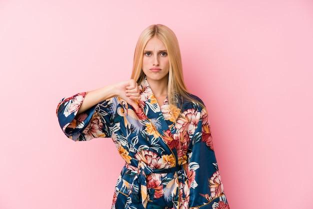 Junge blonde frau, die einen kimono-pyjama zeigt eine abneigungsgeste, daumen unten trägt. uneinigkeit konzept.