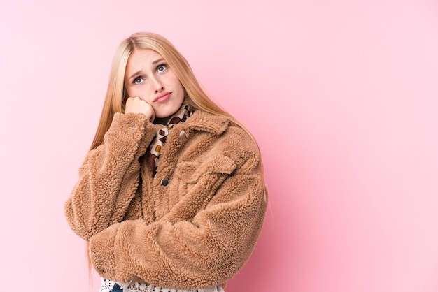 Junge blonde frau, die einen mantel gegen ein rosa trägt, das sich traurig und nachdenklich fühlt und kopierraum betrachtet.