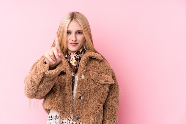 Junge blonde frau, die einen mantel gegen eine rosa wand trägt, die nummer eins mit finger zeigt.