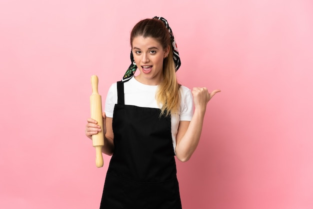 Junge blonde frau, die einen nudelholz lokalisiert auf rosa wand hält, die zur seite zeigt, um ein produkt zu präsentieren
