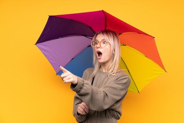 Junge blonde frau, die einen regenschirm hält, der weg zeigt