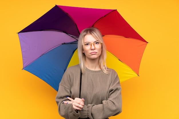 Junge blonde frau, die einen regenschirm über isolierter gelber wand hält, die arme verschränkt hält