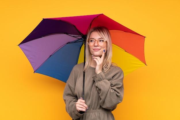Junge blonde frau, die einen regenschirm über isolierter gelber wand hält, die eine idee denkt