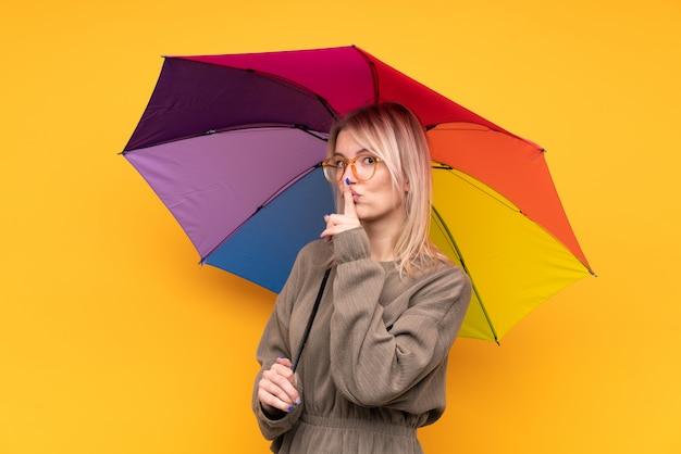 Junge blonde frau, die einen regenschirm über isolierter gelber wand hält, die stille geste tut