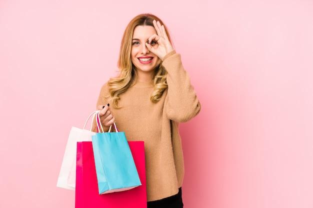 Junge blonde frau, die einkaufstaschen aufgeregt hält, ok geste auf auge halten.