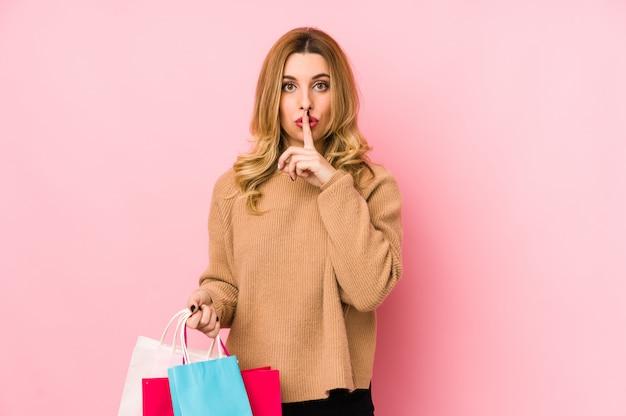 Junge blonde frau, die einkaufstaschen isoliert hält, ein geheimnis hält oder um stille bittet.