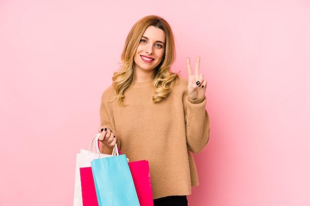 Junge blonde frau, die einkaufstaschen lokalisiert zeigt nummer zwei mit den fingern hält.
