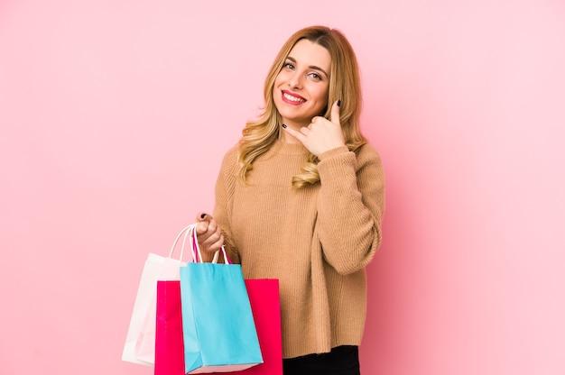 Junge blonde frau, die einkaufstaschen lokalisiert zeigt, zeigt eine handy-anrufgeste mit den fingern.
