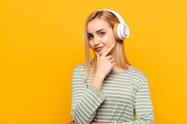 Junge blonde frau, die ernst, nachdenklich und misstrauisch aussieht, mit einem arm verschränkt und hand am kinn, gewichtungsoptionen