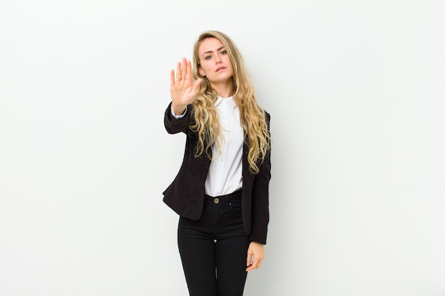 Junge blonde frau, die ernst, streng, unzufrieden und wütend aussieht und offene handfläche zeigt, die stoppgeste gegen weiße wand macht
