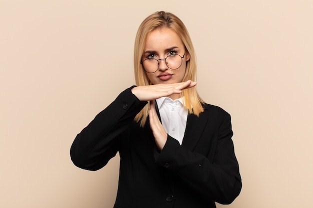 Junge blonde frau, die ernst, streng, wütend und unzufrieden aussieht und auszeitzeichen macht