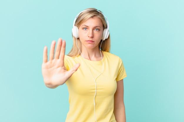 Junge blonde frau, die ernsthafte offene handfläche zeigt, die stoppgeste macht und musik hört.