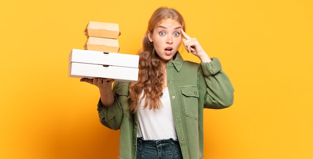 Junge blonde frau, die fast food wegnimmt