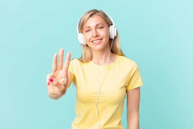 Junge blonde frau, die freundlich lächelt und aussieht, nummer drei zeigt und musik hört.