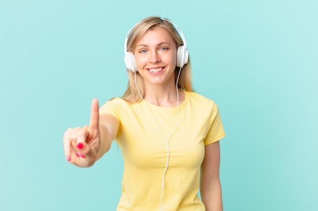 Junge blonde frau, die freundlich lächelt und aussieht, nummer eins zeigt und musik hört.
