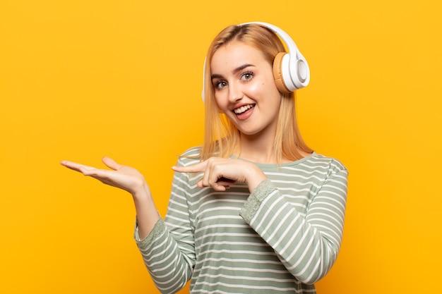 Junge blonde frau, die fröhlich lächelt und zeigt, um raum auf handfläche auf der seite zu kopieren, ein objekt zeigend oder werbend