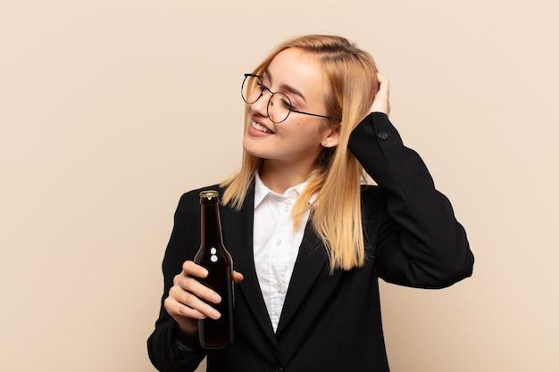 Junge blonde frau, die fröhlich und beiläufig lächelt und hand an kopf mit einem positiven, glücklichen und selbstbewussten blick nimmt