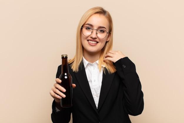 Junge blonde frau, die fröhlich und selbstbewusst mit einem lässigen, glücklichen, freundlichen lächeln lacht