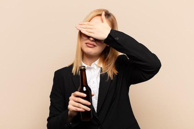 Junge blonde frau, die gesicht mit beiden händen bedeckt, sagt nein zur kamera! bilder ablehnen oder fotos verbieten
