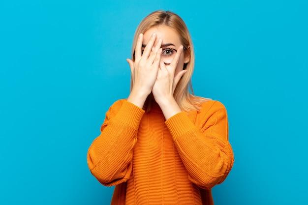 Junge blonde frau, die gesicht mit händen bedeckt, zwischen fingern mit überraschtem ausdruck späht und zur seite schaut