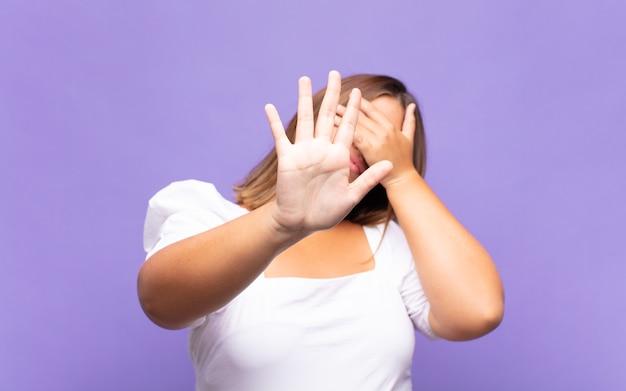 Junge blonde frau, die gesicht mit hand bedeckt und andere hand nach vorne legt, stoppen geste