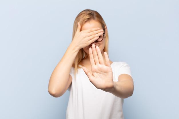 Junge blonde frau, die gesicht mit hand bedeckt und andere hand vorne legt, um kamera zu stoppen, fotos oder bilder ablehnend