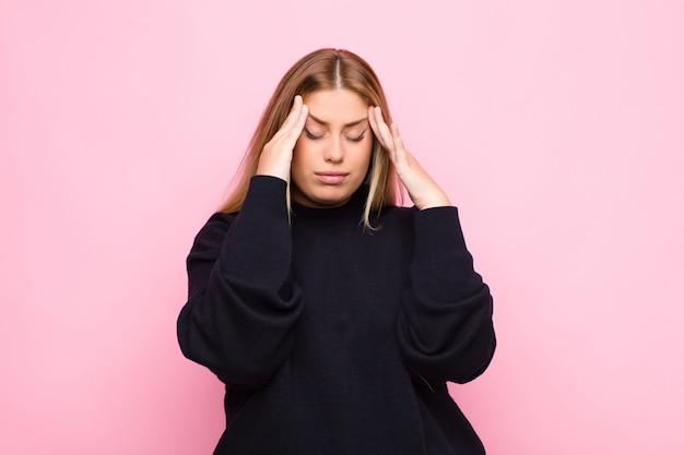Junge blonde frau, die gestresst und frustriert aussieht, unter druck mit kopfschmerzen arbeitet und mit problemen gegen flache wand beunruhigt