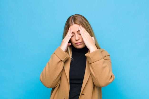 Junge blonde frau, die gestresst und frustriert aussieht, unter druck mit kopfschmerzen arbeitet und mit problemen über der wand beunruhigt ist