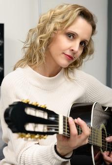 Junge blonde frau, die gitarre spielt