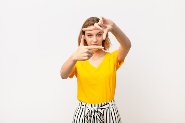 Junge blonde frau, die glücklich, freundlich und positiv fühlt, lächelt und ein porträt oder fotorahmen mit händen gegen flache farbwand macht