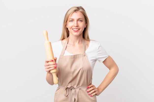 Junge blonde frau, die glücklich mit einer hand auf der hüfte und selbstbewusst lächelt. bäckerkonzept