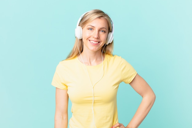 Junge blonde frau, die glücklich mit einer hand auf der hüfte und selbstbewusst lächelt und musik hört.