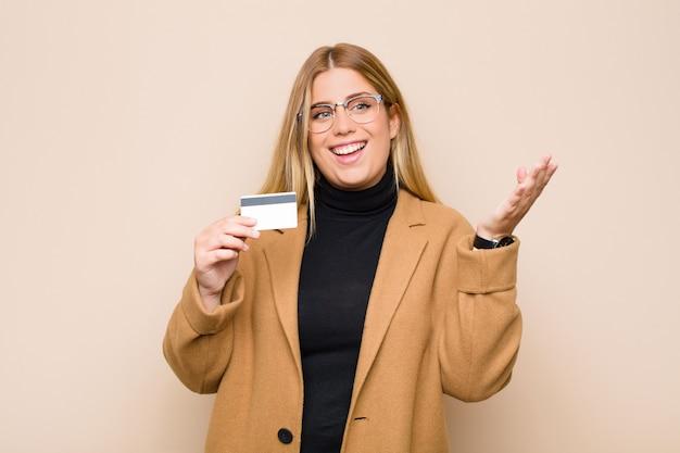 Junge blonde frau, die glücklich, überrascht und fröhlich fühlt, mit positiver einstellung lächelt und eine lösung oder idee mit einer kreditkarte verwirklicht