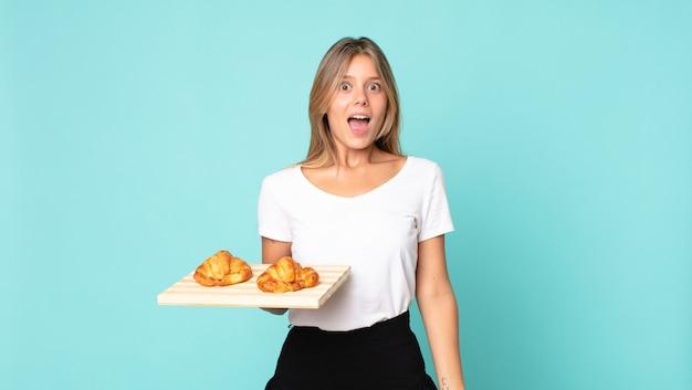 Junge blonde frau, die glücklich und angenehm überrascht aussieht und ein croissant-tablett hält?