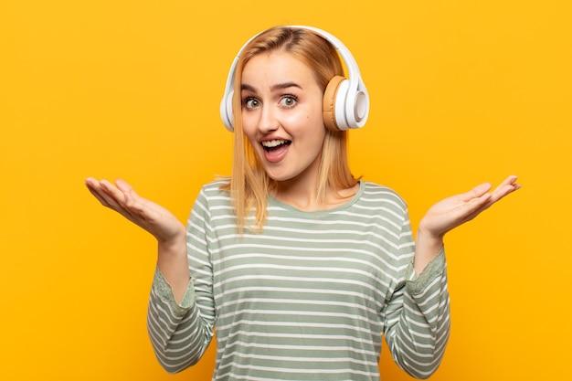 Junge blonde frau, die glücklich und aufgeregt aussieht, schockiert mit einer unerwarteten überraschung mit beiden händen offen neben gesicht