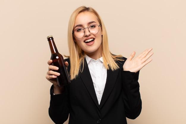 Junge blonde frau, die glücklich und aufgeregt aussieht, schockiert von einer unerwarteten überraschung mit beiden händen offen neben gesicht