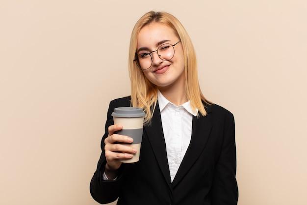 Junge blonde frau, die glücklich und freundlich schaut, lächelt und ihnen mit einer positiven einstellung ein auge zuzwinkert