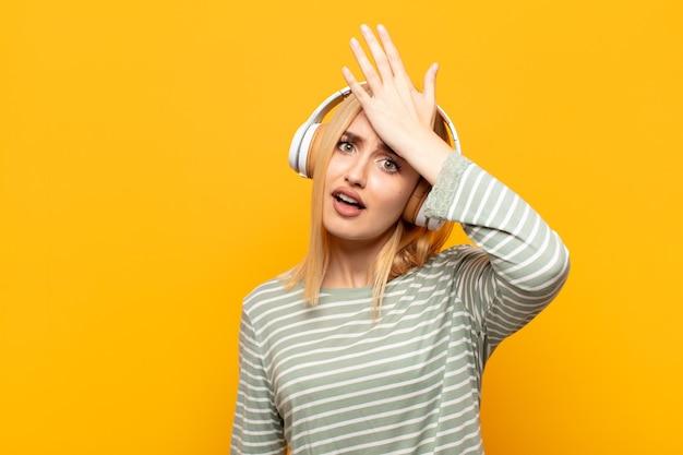 Junge blonde frau, die handfläche zur stirn hebt, die oops denkt, nachdem sie einen dummen fehler gemacht oder sich erinnert hat, sich dumm fühlt