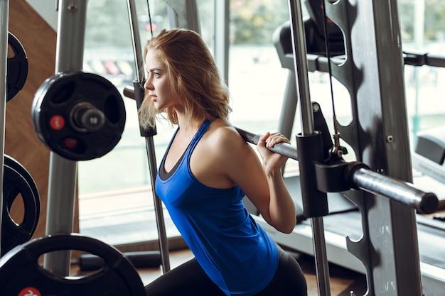Junge blonde frau, die hanteln im fitnessstudio hebt