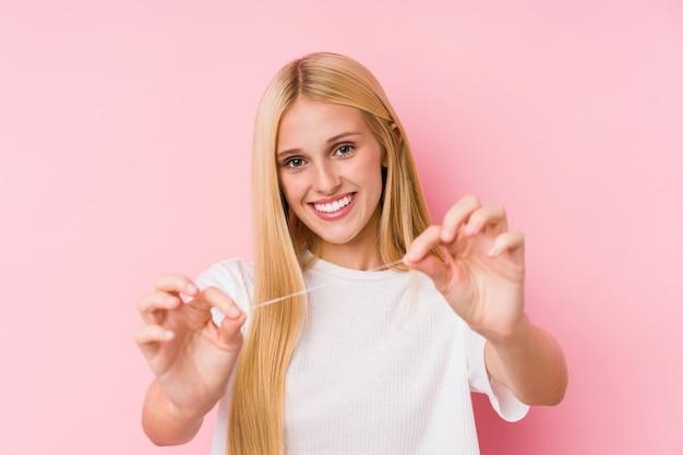 Junge blonde frau, die ihre zähne mit einer zahnseide putzt