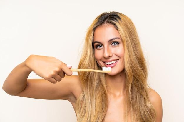 Junge blonde frau, die ihre zähne putzt