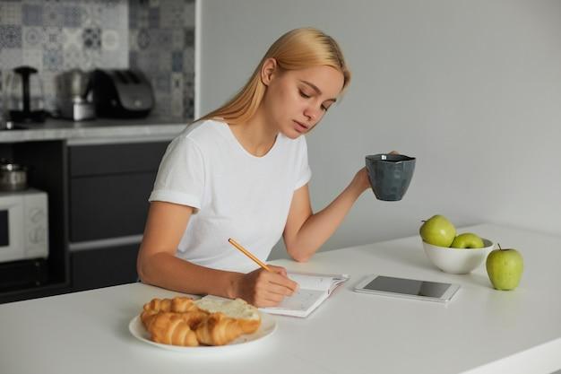 Junge blonde frau, die ihren tag plant, eine große graue tasse hält, pläne in einer molkerei schreibt